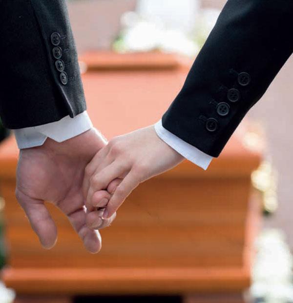 Zwei Hände die einander halten, im Hintergrund ist ein Sarg zu sehen